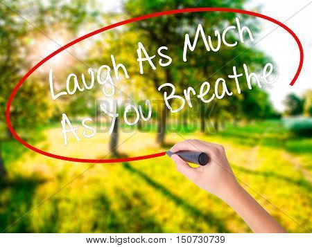 Woman Hand Writing Laugh As Much As You Breathe With A Marker Over Transparent Board .