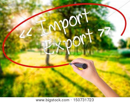 Woman Hand Writing Import - Export With A Marker Over Transparent Board .