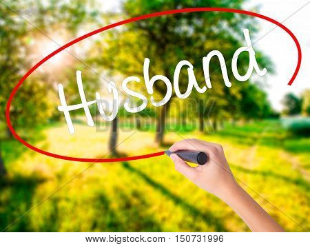 Woman Hand Writing Husband With A Marker Over Transparent Board .