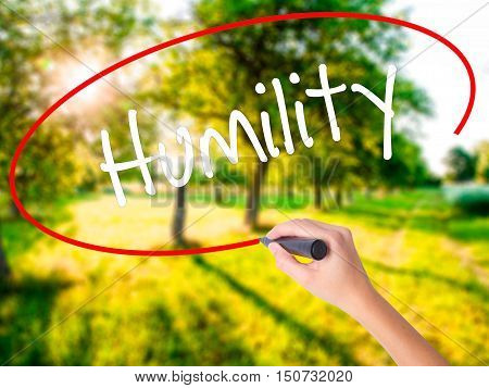 Woman Hand Writing Humility  With A Marker Over Transparent Board .