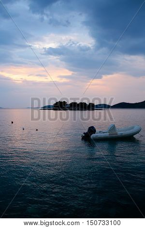 White boat inflatable rubber vessel with motor at anchor in calm blue sea water inshore after sunset on beautiful evening seascape