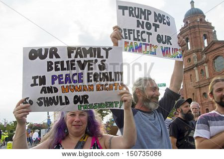 Asheville North Carolina USA: September 12 2016: Donald Trump protesters hold signs about peace equality human rights and family values on Flint Street on September 12 2016 in downtown Asheville NC
