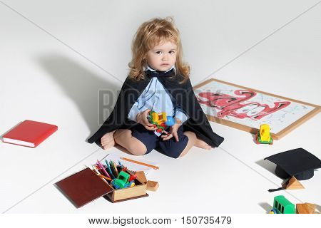 Little boy child in black academic gown playing with drawing school board holding marker near box with colored pencils isolated on white background