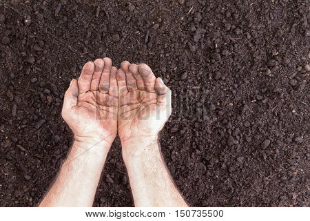 Pair Of Empty Hands Holding Nothing Over Bare Soil