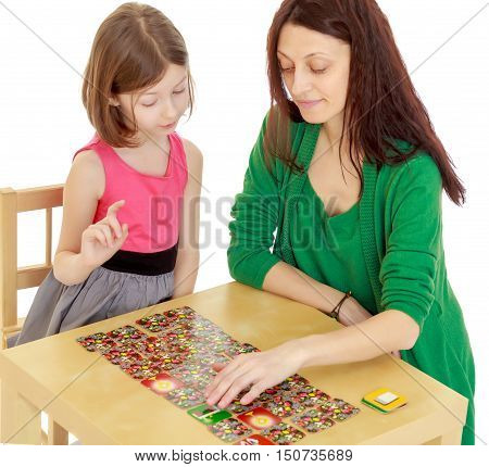 Pensive little girl and her teacher at the table laid out cards with pictures.Isolated on white background.
