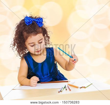 Pensive little girl in a blue dress, holding a pencil . She paints at a table in a Montessori kindergarten.Winter brown abstract background with white snowflakes.