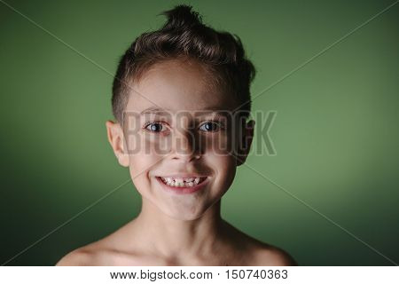 Close up portrait of six-year-old boy with funny hair on green degrade background