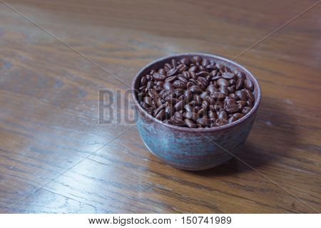 fresh coffee bean seed in rusty coffee cup bowl on wooden table/fresh coffee bean