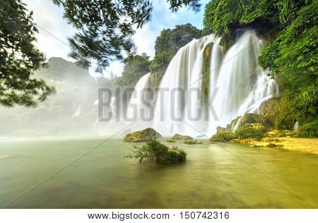 Ban Gioc Waterfall with lakeside tree foreground, smooth flow of water, creating in a waterfall down the white silk sheets high side mountains, sunny yellow iridescent color great lake