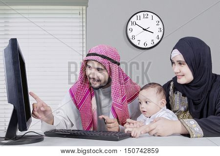 Portrait of happy middle eastern family sitting and using computer for shopping online while holding credit card at the office