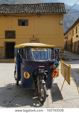 OLLANTAYTAMBO, PERU - OCTOBER 1, 2016: Auto rickshaw in the street of Ollantaytambo, Peru. Ollantaytambo was the royal estate of Emperor Pachacuti who conquered the region.
