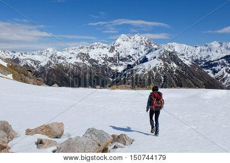 A Woman Hiker Crosses Snow Slopes In View of Mt Rolleston.  Temple Basin, Arthurs Pass, Southern Alps, New Zealand