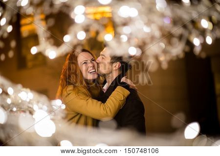 Man kissing woman in street with christmas lights in foreground