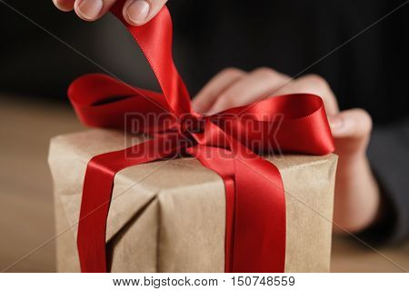 female teen hand going to untie bow on gift box, shallow dof