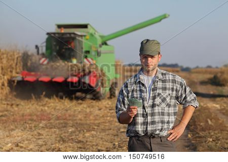 Farmer holding Euro banknote with combine harvester in background corn harvest concept