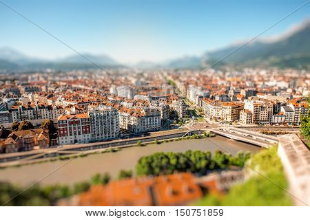 Morning cityscape view on the old town with mountains and river in Grenoble city on the south-east of France. Blurred image with tilt-shift technic