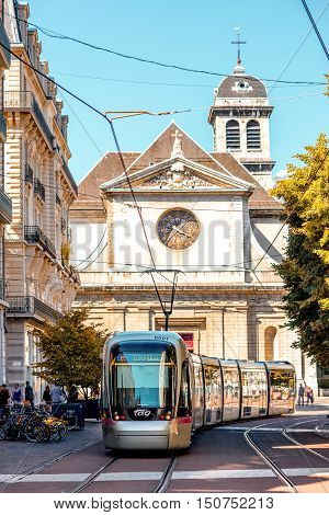 Grenoble, France - June 21, 2016: City street view with Saint Louis church and tram in Grenoble city in France