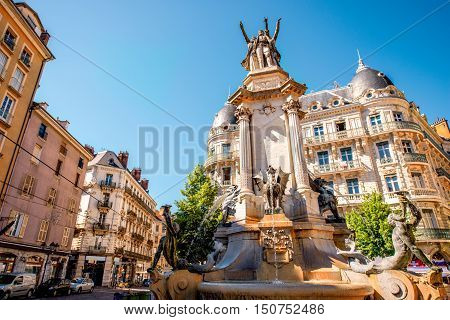 City street view with fountain of Three Orders in the old town of Grenoble city on the soth-east of France