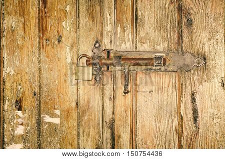 Old latch with padlock on wood door