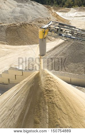 Working belt conveyor and a piles of stone meal in Gravel Quarry