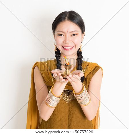 Mixed race Indian Chinese female in traditional dress hands holding diya oil lamp and celebrating Diwali or deepavali, fesitval of lights.