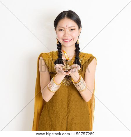 Mixed race Indian Chinese girl in traditional dress hands holding diya oil lamp and celebrating Diwali or deepavali, fesitval of lights.