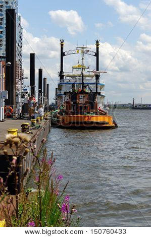 HAMBURG, GERMANY - JULY 18, 2015: a yellow Tug Boat in the port of Hamburg at the pier with flowers in front.