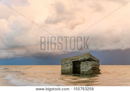 Ruins in the sea with storm clouds and dramatic sunset sky.
