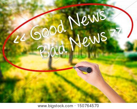 Woman Hand Writing Good News - Bad News With A Marker Over Transparent Board .