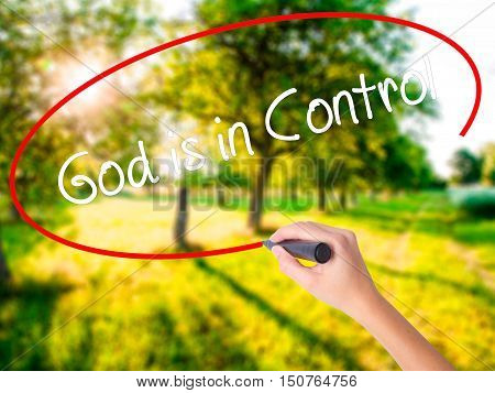 Woman Hand Writing God Is In Control With A Marker Over Transparent Board