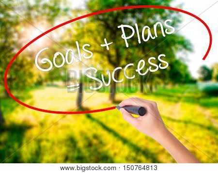 Woman Hand Writing Goals + Plans = Success With A Marker Over Transparent Board .