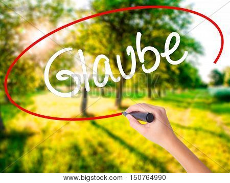 Woman Hand Writing Glaube (believe In German) With A Marker Over Transparent Board .