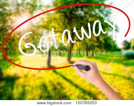 Woman Hand Writing Getaway With A Marker Over Transparent Board