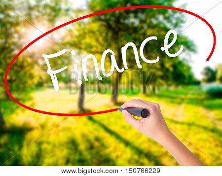 Woman Hand Writing Finance With A Marker Over Transparent Board .