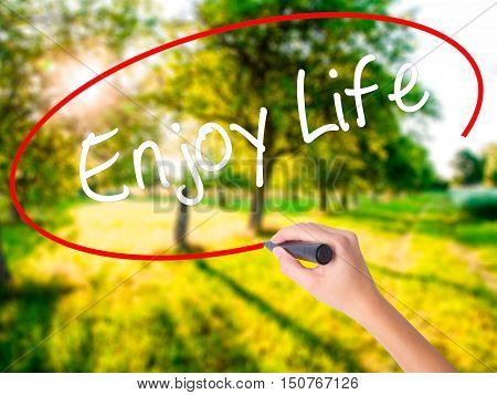 Woman Hand Writing Enjoy Life With A Marker Over Transparent Board