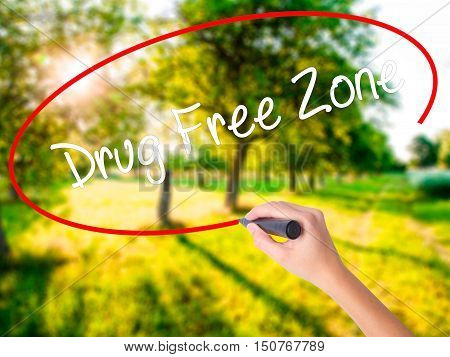 Woman Hand Writing Drug Free Zonewith A Marker Over Transparent Board