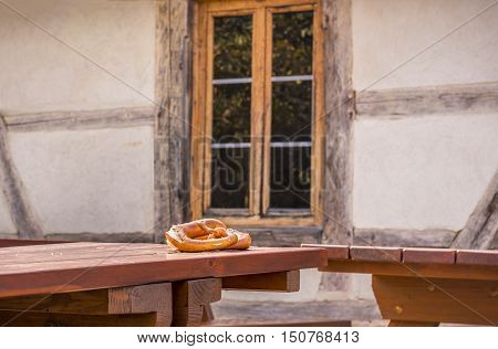 Pretzel on table in a rustic German decor - Two pretzels a specific German pastry product on a wooden table in front of an old rustic house with German traditional features.