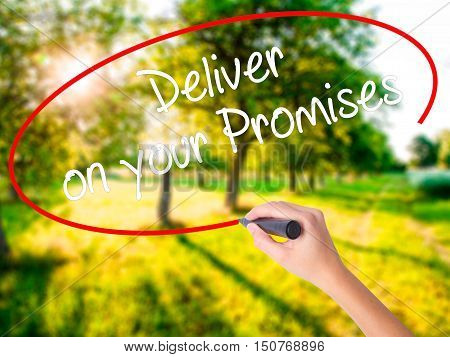 Woman Hand Writing Deliver On Your Promises With A Marker Over Transparent Board