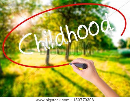Woman Hand Writing Childhood With A Marker Over Transparent Board