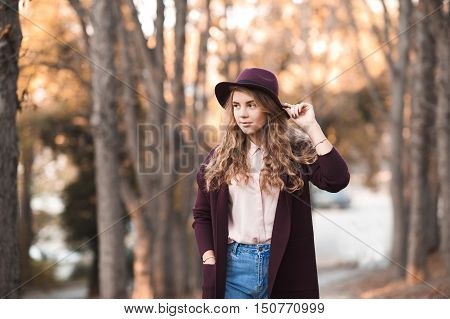 Stylish teenage girl 14-16 year old wearing winter jacket and hat outdoors.