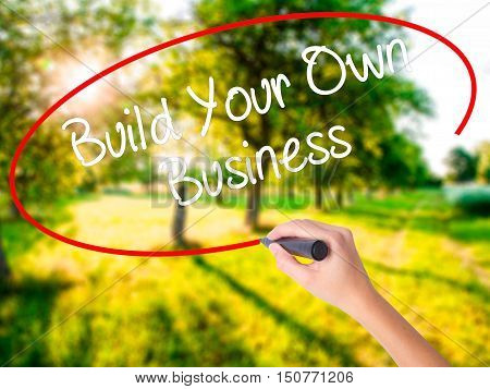 Woman Hand Writing Build Your Own Business With A Marker Over Transparent Board .