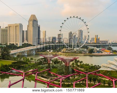 SINGAPORE, REPUBLIC OF SINGAPORE - JANUARY 09, 2014: Singapore city skyline and Singapore Flyer at sunset. View from Supertree rooftop