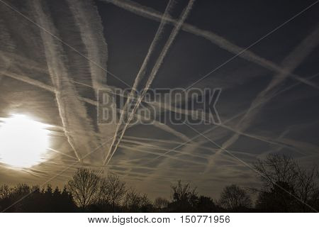 Crossing contrails on a dark sky at sunrise