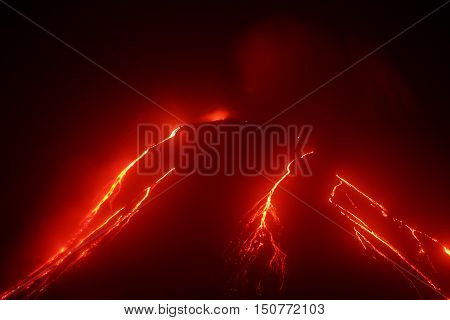 Volcanic landscape of Kamchatka: night view of eruption Klyuchevskaya Sopka current lava flows on the of the volcano. Russian Far East Kamchatka Region Klyuchevskaya Group of Volcanoes.