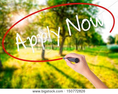 Woman Hand Writing Apply Now With A Marker Over Transparent Board