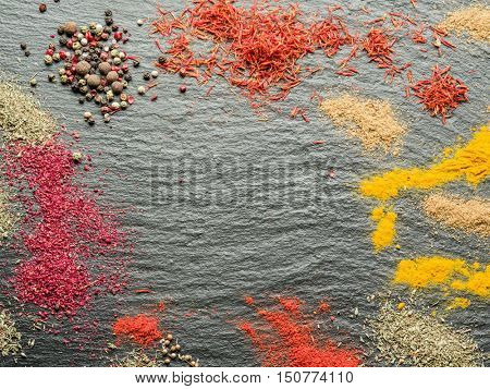 Assortment of colorful spices on the graphite background.