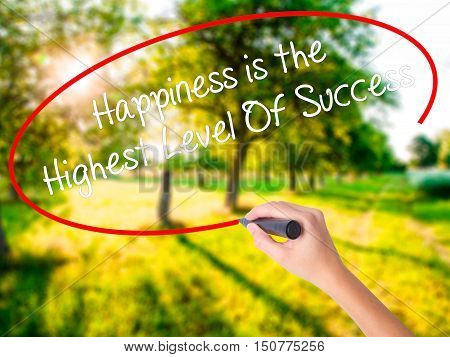 Woman Hand Writing Happiness Is The Highest Level Of Success With A Marker Over Transparent Board