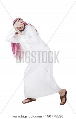 Scared Arabian businessman running away from something isolated on white background