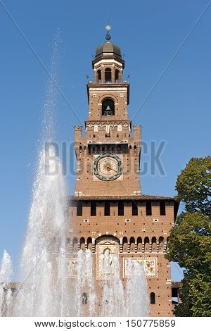 Detail of the clock tower of the Sforza Castle XV century (Castello Sforzesco) and the fountain. It is one of the main symbols of the city of Milan Lombardy Italy