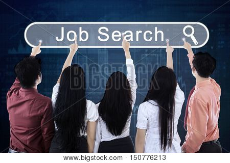 Rear view of businesspeople touching a virtual job search button on the virtual screen. Concept of Job Search